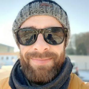 Mann mit Bart, Sonnenbrille und Schal im Winter