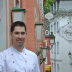 Ein Koch vor dem Restaurant in einer Gasse als Referenzfoto für das Online Marketing.